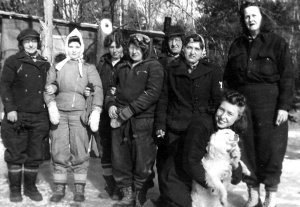 The crew of the women's sawmill at Turkey Pond assemble for a picture on January 14, 1943. Left to right: Mary Plourde, Barbara Webber, Violet Story, Carmilla Wilson, Lucy DeGreenia, Ruth DeRoche, Daisy Perkins, Laura Willey, and Chimney the dog. Credit: Courtesy of John Willey.